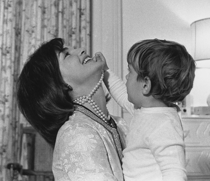 First Lady Jacqueline Kennedy laughs as her son John Kennedy Jr. plays with her simulated-pearl necklace in White House